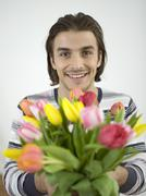Man holding bunch of flowers Stock Photos