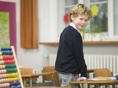 Boy in class room, abacus on desk Stock Photos