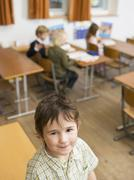 Pupils in class room, boy looking to camera Stock Photos