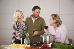 Parents with daughter in kitchen, smiling Stock Photos