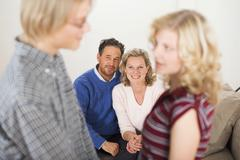 Teenage couple, parents sitting in background Stock Photos