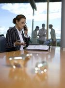Business womn in office, figurines of bull and bear on desk Stock Photos