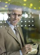 Young businessman standing behind glass pane - stock photo