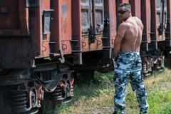 Muscular man pissing on railroad Stock Photos