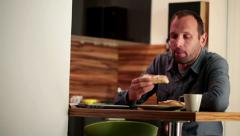 Stock Video Footage of Young man eating sandwich and drinking tea at the kitchen table HD
