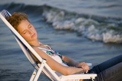 Young woman sitting in deck chair on beach - stock photo