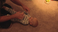 Father playing with his baby boy before bed Stock Footage