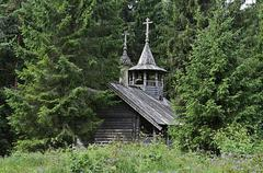 old wooden chapel in the forest - stock photo