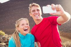 Young attractive athletic couple taking photo of themselves with smart phone Stock Photos