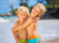 two young boys having fun on tropcial beach - stock photo