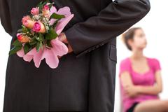man hiding flowers - stock photo