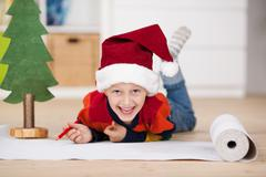 playful young boy in a santa hat - stock photo