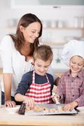 two young brothers baking with their mother - stock photo