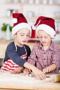 two little brothers cutting out christmas cookies - stock photo