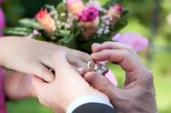 Stock Photo of wedding ring putting
