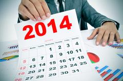 man in suit with charts and a 2014 calendar - stock photo