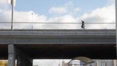 Man walking across the bridge Stock Footage