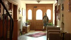 Girl with a backpack running down the stairs and out of home - view from inside. - stock footage