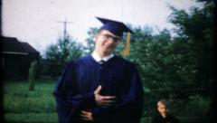 The graduate poses for the camera in cap and gown, 585 vintage film home movie Stock Footage