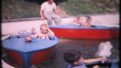 Children enjoy boat rides at local amusement park, 581 vintage film home movie  Stock Footage