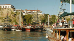Tourists returning to harbor after a sea voyage on the old-style wooden ship - stock footage