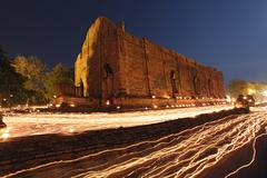 Candle light trail of buddhism ceremony at temple ruin at dusk on asalha puja Stock Photos