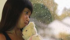 Sad Asian Girl Kisses Teddy Bear By Window Stock Footage