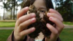Cute Little Girl Holding Pine Cones Stock Footage