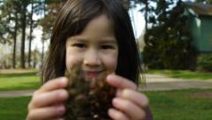 Stock Video Footage of Cute, Smiling Little Girl Holding Pine Cones