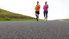 Low Angle Of Fit Young Couple Running Down Road (Slow Motion) Stock Footage