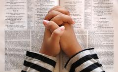 hand's clasped in prayer lie on the bible - stock photo