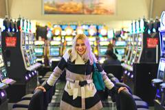 happy girl near the slot machines at the airport in las vegas - stock photo
