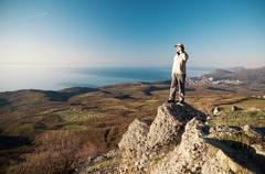 man with mobile phone on the top of world - stock photo