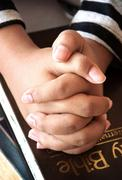Young girl's hands clasped in prayer over a holy bible. Stock Photos
