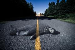 empty road with dead body's ghost in the middle - stock photo