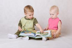 Boy and the girl sit on a floor and read the book Stock Photos