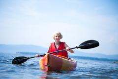 woman with safety vest kayaking alone on a calm sea - stock photo