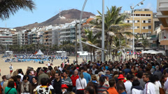 People enjoy a sunny day walking the promenade at Beach of the Canteras Stock Footage