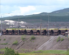 Iron ore shuttle train carriages riding in mining landscape, Kiruna, Sweden Stock Footage