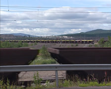 Iron ore train riding along highway in mining landscape, Kiruna, Sweden Stock Footage