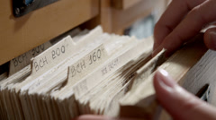 Girl student looking for a book in the library card catalog 2 - stock footage