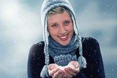 young cute woman with a hand full of snow - stock photo