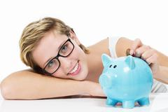 smiling woman throwing money in her piggybank - stock photo