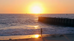 Girl with Long Hair Spinning in Beach Waves at Sunset - Wide Shot Playa Del R - stock footage