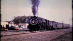 613 - trains come by the station one after the other - vintage film home movie  - stock footage