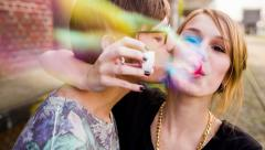 3Young teenage girl and her boyfriend blowing bubbles Stock Footage