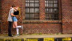Teenage couple kissing in front of old industry building - stock footage