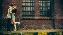 Teenage couple kissing in front of old industry building Stock Footage