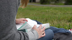 Girl reading bible outside (outdoors) on lap, dolly shot (devotions) Stock Footage