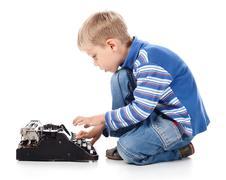 Boy typing on old typewriter Stock Photos